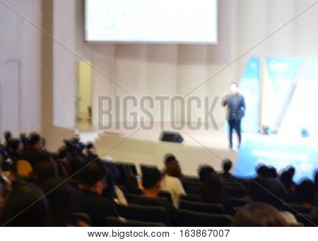 Speaker giving a talk at business meeting and audience in the conference hall blur background, business conference and presentation