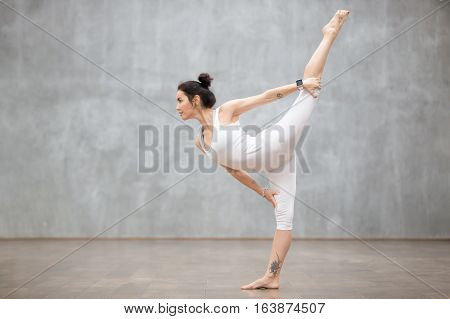Profile portrait of beautiful young woman wearing white sportswear working out against grey wall, doing yoga or pilates exercise. Standing in variation of Natarajasana, Lord of the Dance. Full length