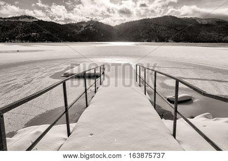 A B&W of a dock on frozen Spirit Lake during winter in Spirit Lake Idaho.