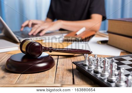 Close Up Gravel Wooden On Business Lawyer Desk With Chess, Law Book, And Businessman Using Laptop As
