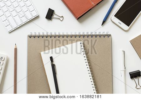 Blank White Notepaper On Brown With Office Supples Around These Desk, View From Above