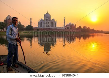 Agra, India - November 8: Unidentified Man Steers Boat On Yamuna River At Sunset In Front Of Taj Mah