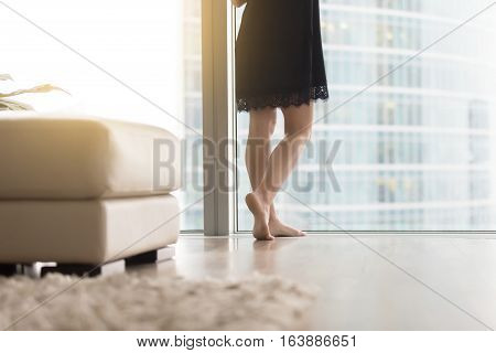 Close up of female bare legs near full length window, relaxing after work day been full of meetings and running around, soft carpet and clean floor, comfortable living space, cleaning service