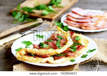 Delicious bacon omelette. Fried omelette with bacon and parsley for breakfast. Bacon slices on a plate, knife, fork, fresh parsley sprigs on old wooden table. Vintage style. Closeup