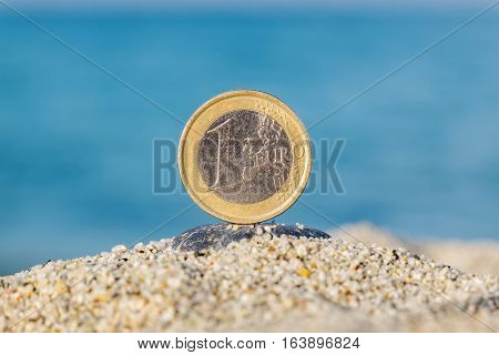 One Euro coin in the sand against blue sea