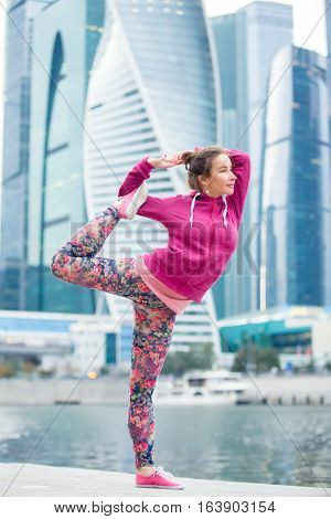 Young attractive woman practicing yoga, standing in Lord of the Dance exercise, Natarajasana pose, working out wearing pink sportswear, outdoor full length, modern skyscraper and river background