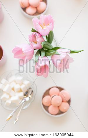 Spring background. Sweets and tea on a table with pink tulips. Still life with fresh bouquet of tulips. Beautifully decorated tray with a bouquet of tulips and a Cup of tea.
