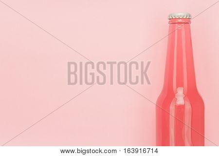 glass bottle of pinkish soda drink on pink background