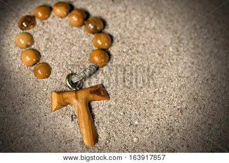Tau wooden cross in the shape of the letter t (symbol of St. Francis of Assisi) with rosary bead partially buried in the sand