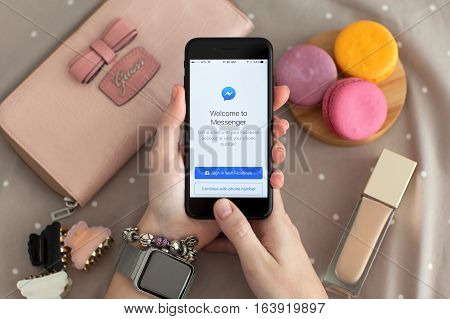 Alushta Russia - November 11 2016: Woman hand with Apple Watch holding iPhone 7 Jet Black with social networking service Facebook Messenger on the screen.