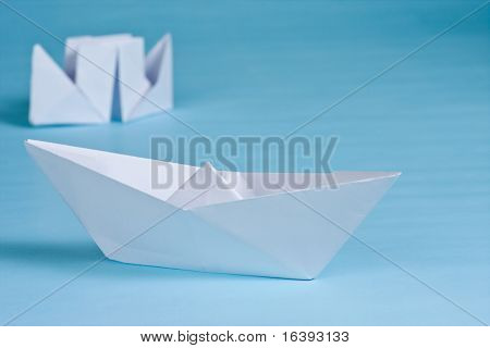 two paper boats on blue background