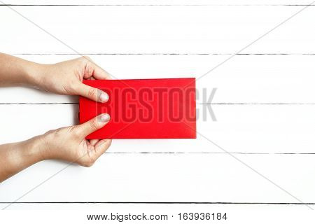 Red Envelope or red packet for Chinese New Year Gifts held in hand on the white wooden plank background Traditional Celebration Chinese New Year.