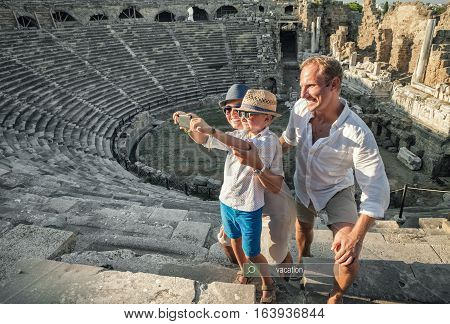 Young positive family take a self photo on the antique sights in Side Turkey