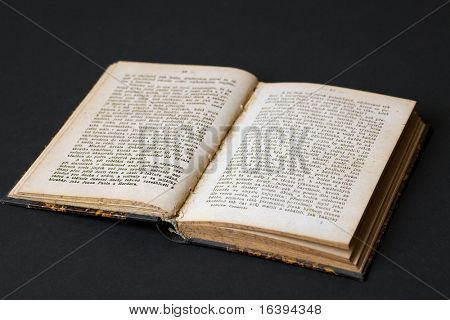 opened old book on black background
