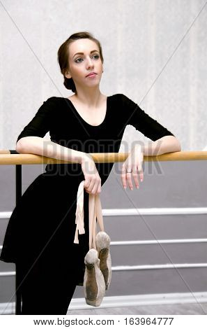 Graceful Ballerina Standing Near The Ballet Barre In A Beautiful Ballet Posture,  Leaned Against Wit