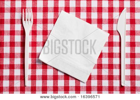 the plastic cutlery on checkered tablecloth