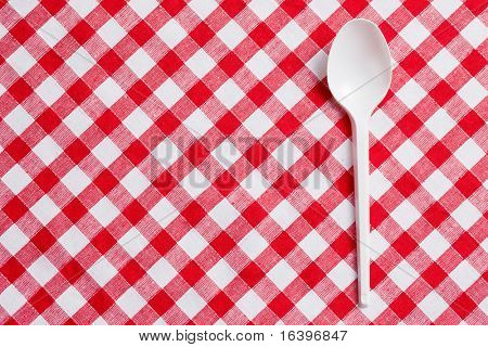the plastic spoon on checkered tablecloth