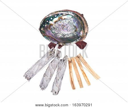 Sage smudge stick, bright polished rainbow abalone shell with wooden cobra stand and palo  santo smudging sticks isolated on white background