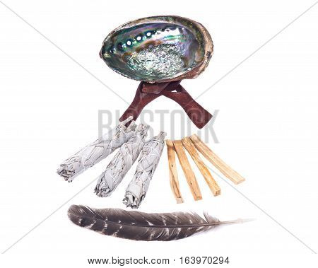 Sage smudge stick, bright polished rainbow abalone shell with wooden cobra stand, grade A barred turkey smudging feather and palo santo smudging sticks isolated on white background