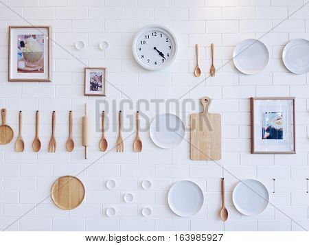 Kitchenware, photo frame and clock hanging on white brick wall, vintage style