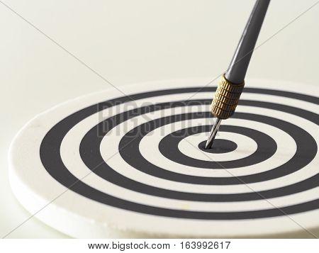 Black and white bullseye dart arrow hitting target center of dartboard. Concept of success target goal achievement. (selective focus)