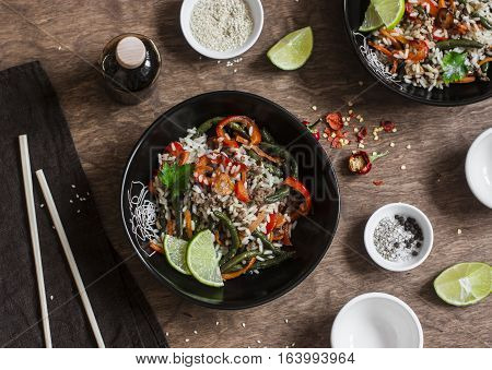 Pork vegetables rice stir fry. On a wooden table top view. Flat lay