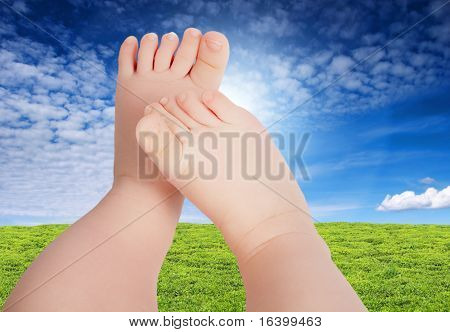 Baby legs against blue sky and green meadow background