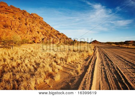 Desert landscape with dusty road and blue sky