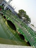 image of muharram  - wooden bridge over the garden canal with its reflection in water at chota imambada lucknow - JPG