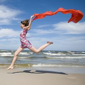 stock photo of rapture  - Happy girl jumping with scarf on the beach - JPG