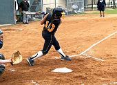 stock photo of fastpitch  - Fastpitch softball girl after having made contact with softball in mid swing - JPG