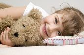 stock photo of night gown  - Little girl with teddy bear on sofa - JPG