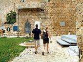 Tourists Walking Beside Acre Castle In Israel poster