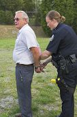 stock photo of crime scene  - Police woman arresting suspect at the crime scene - JPG