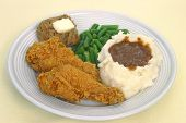 picture of fried chicken  - A dinner of fried chicken and mashed potatoes with brown gravy green beans and a roll with butter - JPG