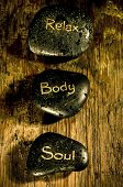 wellness and reiki concept with three black massage stones with words soul, body, relax and drops of