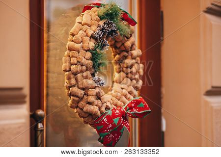 poster of Creative Christmas Wreath Of Wine Corks, Pine Cones And Red Bows On Door Or Window  Of Wine Store In