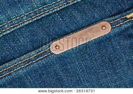 Bronze metal label on blue jeans