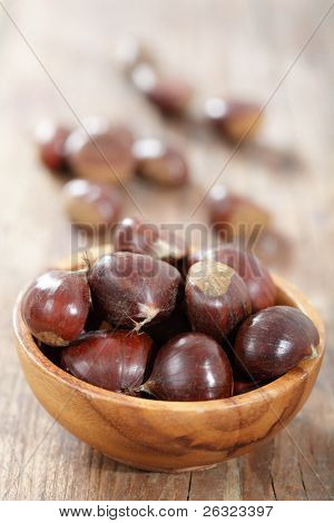Sweet chestnuts in the wooden bowl on the rustic table