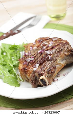 Grilled rib steak with red onion and rocket salad