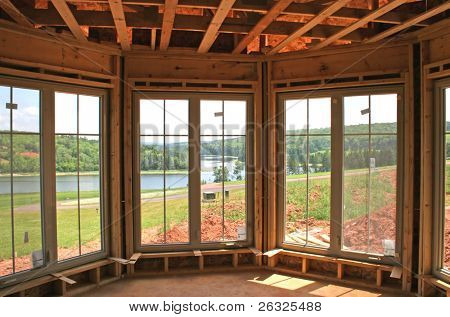 The interior of a partially constructed house showing the new windows and a lovely river view.