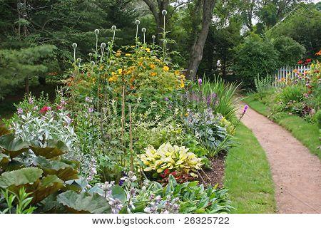 Um caminho através de um parque cercado por colorido perenes camas.
