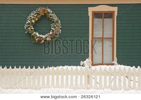 A Christmas wreath on an old Victorian house which is surrounded by a picket fence and snow.