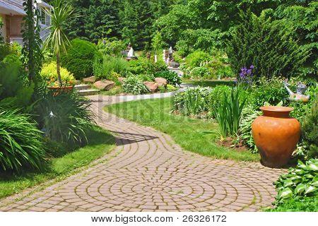 A stone walkway meandering through a garden.