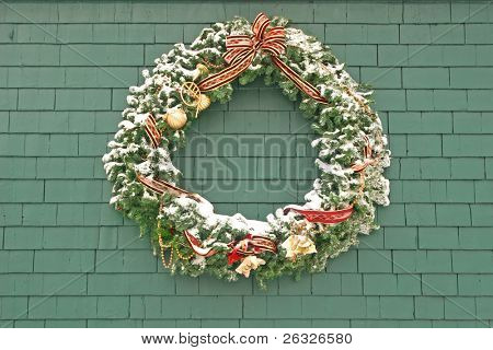 A snow covered Christmas wreath made of spruce and decorated and hung outside on the side of a building.