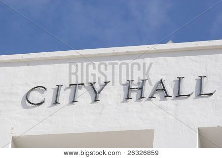 City hall sign on a modern white stucco building.
