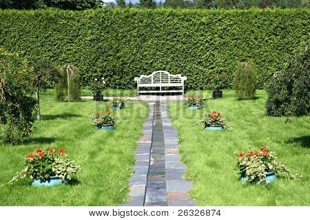 A wooden bench in a formal garden or park.