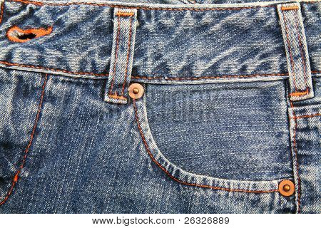 The detail on a the front of a worn pair of blue jeans.