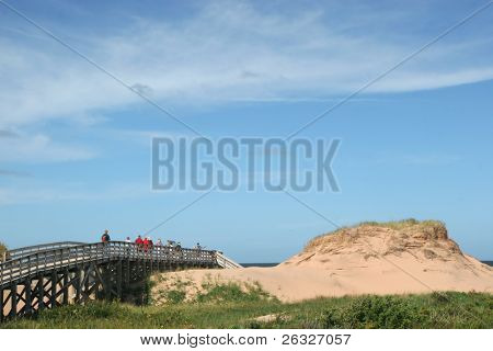 People walking over the boardwalk through the sand dunes to the beach in Cavendish National Park, Prince Edward Island, Canada.