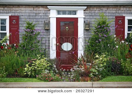 The entrance to a home surrounded by yew shrubs and annual and perennial flowers.